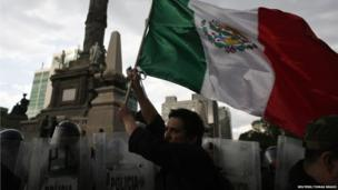 A demonstrator holds a Mexican national flag in front of riot policemen during a protest against the privatisation of the state oil monopoly Pemex at the Angel of Independence in Mexico City, 1 July