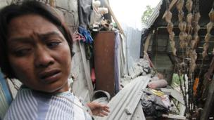 An Acehnese resident looks at her quake-damaged house at Lampahan village in Aceh province, Indonesia, 2 July 2013