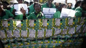 Women of the ANC Women's League sing and hold posters at the entrance of the Mediclinic Heart Hospital, where Nelson Mandela is being treated, Pretoria, South Africa, 4 July 2013