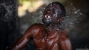 A Zimbabwean man is baptised during a service in the Yeoville neighbourhood, 4 July 2013, in Johannesburg, South Africa