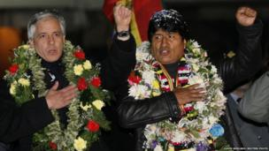 Bolivia's President Evo Morales (right) and Vice-President Alvaro Garcia Linera sing the national anthem after Mr Morales' arrival at the El Alto airport on the outskirts of La Paz, 4 July 2013