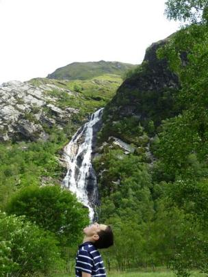 Boy standing in front of a waterfall