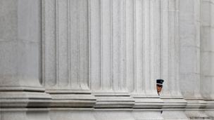 A security guard stands at a bank in front of the Bank of Japan headquarters in Tokyo