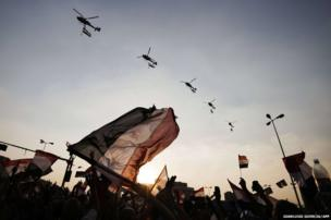 """Egyptian people wave the national flag as army helicopters fly above Egypt""""s landmark Tahrir square"""