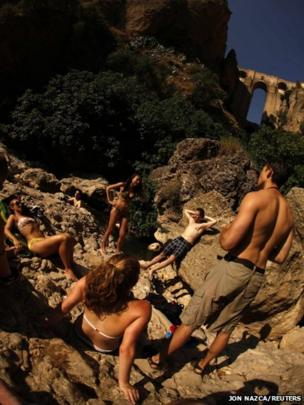 Tourists sunbathe after cooling off in a pool