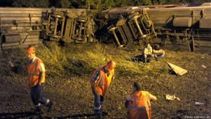 Workers rest at the scene of a train crash in the Krasnodar region