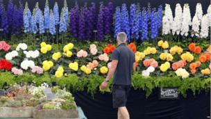 Finishing touches are made to a floral display at the RHS Hampton Court Palace Flower Show
