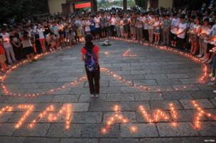 Students light candles in remembrance of colleagues