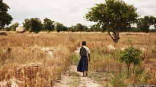 Tanzanian schoolgirl Sylvia walking through a field of scrub by her home to the road