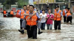 A policeman carries a man on his back as he walks on a flooded street after heavy rainfalls hit Chengdu, Sichuan province, 9 July 2013