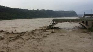 In this image taken by mobile phone camera, what remains of the Qinglian bridge that was swept away by heaving flood waters is seen in the city of Jiangyou in Sichuan on 9 July 2013
