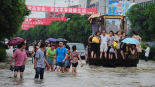 Residents travel on an excavator as others commute through flooded streets in a district in Chengdu, southwest China's Sichuan province.