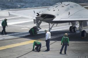 Air wing maintenance personnel check the arresting line after the X-47B Unmanned Combat Air System