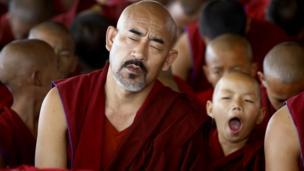 A young Tibetan Buddhist monk yawns
