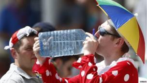 An England fan wearing fancy dress drinks water