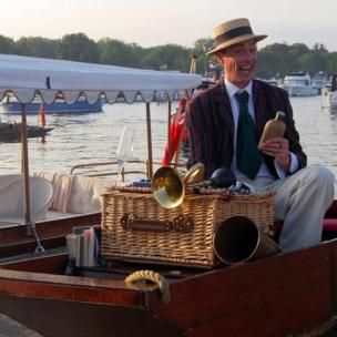"An actor taking part in the Henley Festival ""roving eccentrica"" aboard a motorised punt."