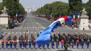 A paratrooper lands on Concorde Square during the Bastille Day parade.