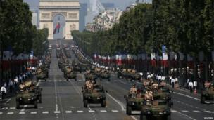 Armoured army vehicles descend from the Champs Elysees.