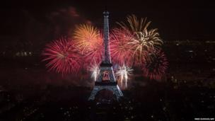 Fireworks burst around the Eiffel Tower
