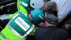 Nigel Dodds being treated by paramedics