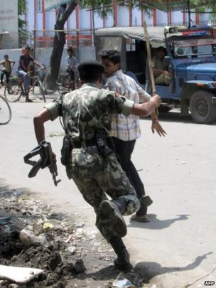 Policeman chases young male youth participating in street protests over school children deaths in Saran district of Bihar state on 17 July