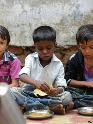 Indian schoolchildren at a school in Ahmedabad eat their free mid-day meal on 17 July 2013