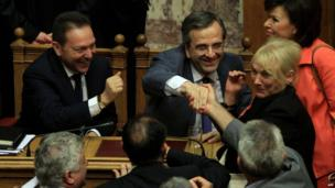 Greek Finance Minister Yannis Stournaras (left) and Greek Prime minister Antonis Samaras (centre) are congratulated by lawmakers after a parliament vote in Athens