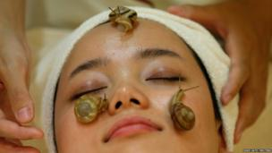 Snails crawl on the face of a woman during a demonstration of a new beauty treatment