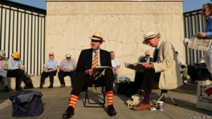 Members of Marylebone cricket club wait to enter Lord's cricket ground in London
