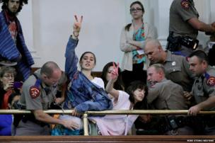 Abortion rights activists disrupt the special session of the Senate to consider legislation restricting abortion rights as they chain themselves to the railing in Austin, Texas.