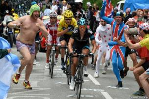 Spectators run alongside riders in the Tour de France