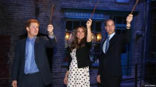 Prince Harry, the Duchess of Cambridge and Prince William, raise their wands on the set used to depict Diagon Alley in the Harry Potter Films on 26 April 2013