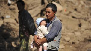 A man holds a baby after an earthquake in Minxian county, Dingxi, Gansu province, July 22, 2013