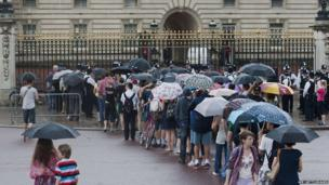 Members of the public and tourists queue in the rain outside Buckingham Palace to look at an easel announcing the birth of Prince William and Catherine, Duchess of Cambridge's new baby boy