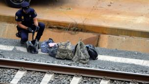 Policeman checking bags by the track