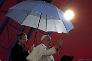 Side lit by a stage light Pope Francis addresses the youth gathered at the World Youth Day Welcome Feast on the Copacabana beachfront in Rio de Janeiro, Brazil