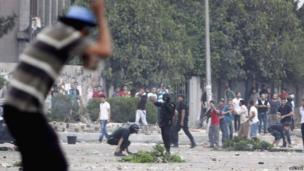 Police officer aims shotgun at protesters in Cairo (27 July 2013)