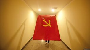A large communist flag being carried along a corridor by a participant at Vietnam's 11th party congress