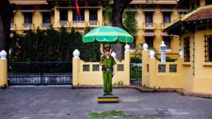 A police officer stands in front of a government building in Hanoi.