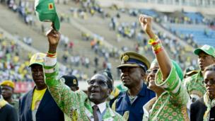 Zimbabwe's President Robert Mugabe (L) and his wife Grace (R) greet supporters after his address at a rally in Harare on 28 July 2013, ahead of elections