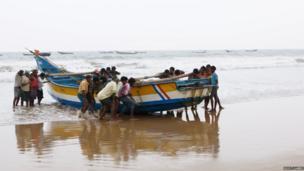 Men lift a boat in in Andhra Pradesh, India