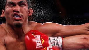 Argentina's Mauricio Munoz takes a punch