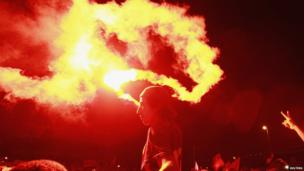A demonstrator holds up a flare in Tunis on 29 July 2013