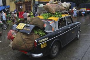 A Premier Padmini taxi overloaded with vegetables drives through a street in Mumbai.