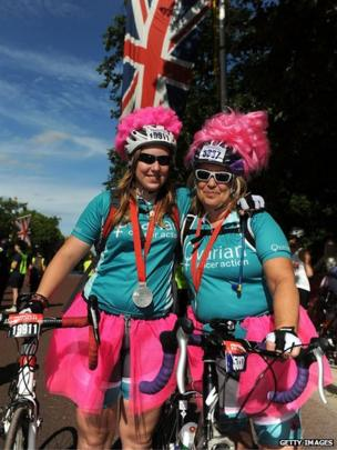Cyclists in pink wigs pose after finish line