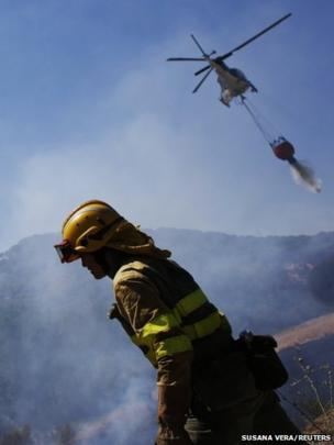 A helicopter dumps water near a firefighter as they try to control a wildfire outside Cebreros, in north western Spain