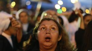 A woman looks up during the festivities for the patron saint of San Salvador