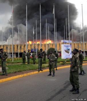 Armed policemen cordon off the area as fire rages at the international arrivals unit of Jomo Kenyatta International Airport, Nairobi, Kenya