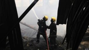 """Firefighters struggle to put out a fire at the Jomo Kenyatta International Airport in Kenya""""s capital Nairobi 7 August 2013."""