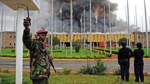 A General Service (GSU) officer gestures outside the burning Jomo Kenyatta international airport on 7 August 2013.
